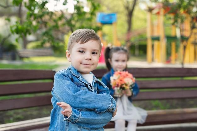 Menino posa no fundo de uma menina com um buquê de flores