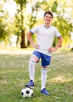 Menino posando ao ar livre com uma bola de futebol