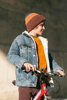 Menino posando com sua bicicleta ao ar livre na cidade