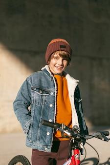 Menino posando com sua bicicleta lá fora na cidade