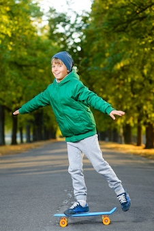 Menino posando de skate ao ar livre