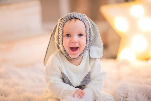 Menino posando em um quarto branco com fundo de natal