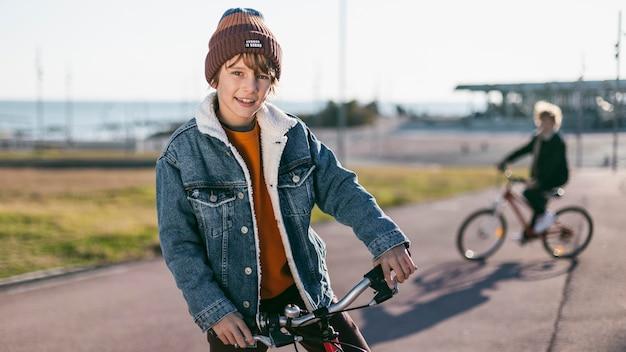 Menino posando enquanto seu amigo está andando de bicicleta