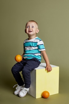 Menino posando, modelo de menino de emoções alegres. uma linda criança brinca de pular e fazer careta sentada em um cubo sobre um fundo brilhante