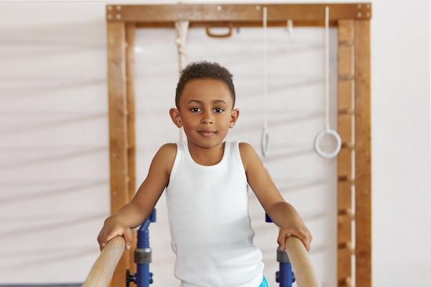 Menino positivo de pele negra e sorridente com camiseta branca se exercitando em duas barras paralelas de madeira