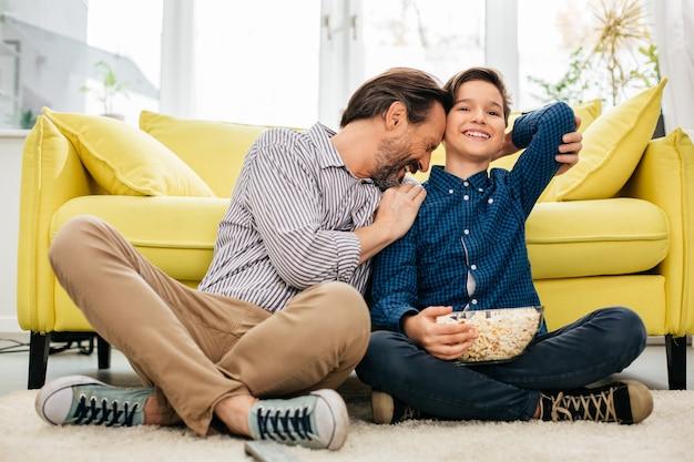Menino positivo sorrindo e segurando uma tigela de pipoca enquanto seu pai emocionado o abraça depois de assistir a um jogo de futebol emocionante