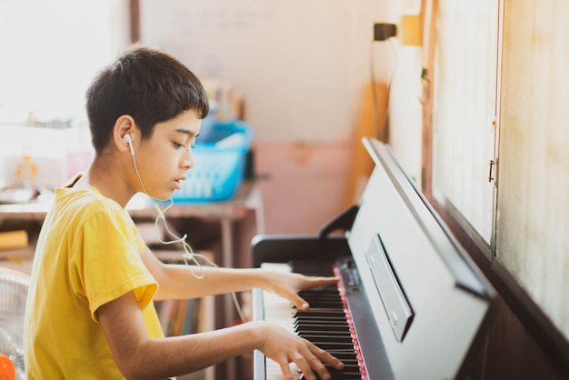 Menino praticando piano tablet digital on-line em casa