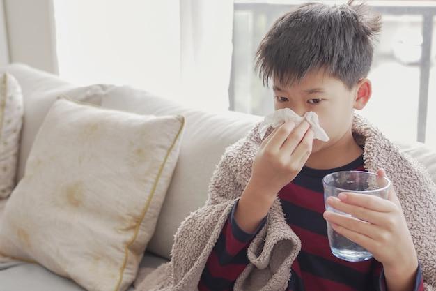Menino pré-adolescente doente assoando o nariz e segurando um copo d'água em casa