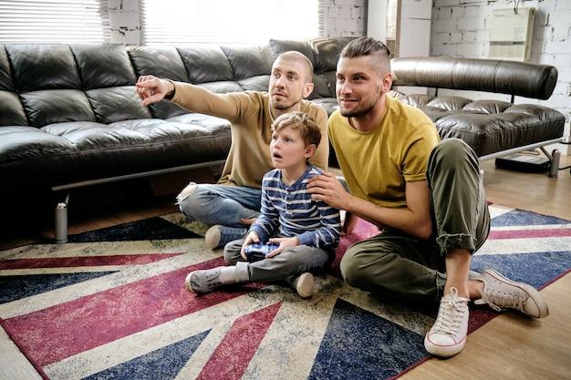 Menino pré-adolescente espantado e dois rapazes sentados no chão jogando videogame novo em casa