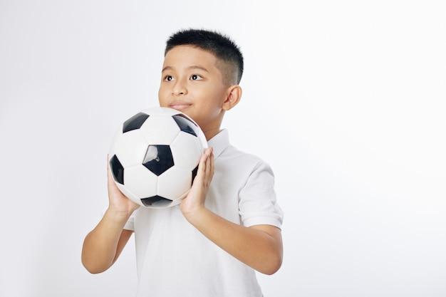 Menino pré-adolescente vietnamita sorridente pronto para jogar uma bola de futebol, isolado no branco