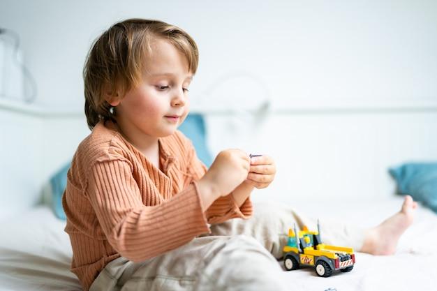 Menino pré-escolar brincando com o construtor, sentado em uma cama na sala. criança passando algum tempo durante a quarentena. conceito de jogos de desenvolvimento, espaço de cópia.