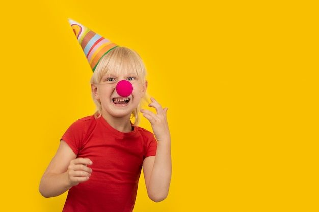 Menino pré-escolar com chapéu festivo e nariz de palhaço vermelho está se divertindo. retrato de criança em fundo amarelo.