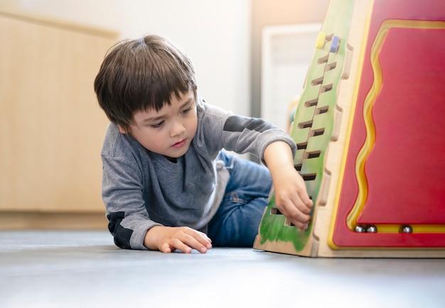 Menino pré-escolar do retrato interior que joga no clube da criança com tom do vintage, criança que diverte-se jogando brinquedos coloridos na sala de jogos da criança.