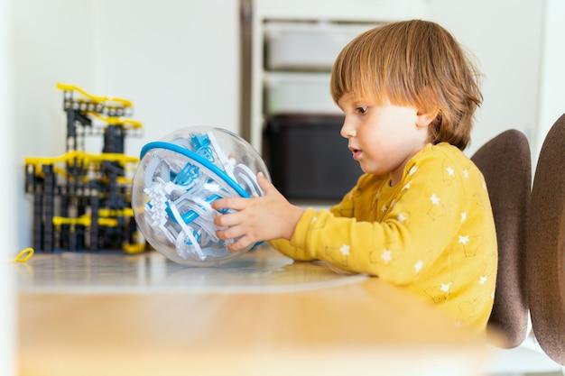 Menino pré-escolar sentado à mesa em uma sala e jogando um jogo de labirinto com obstáculos. criança aprendendo em casa. educação precoce. garoto inteligente.