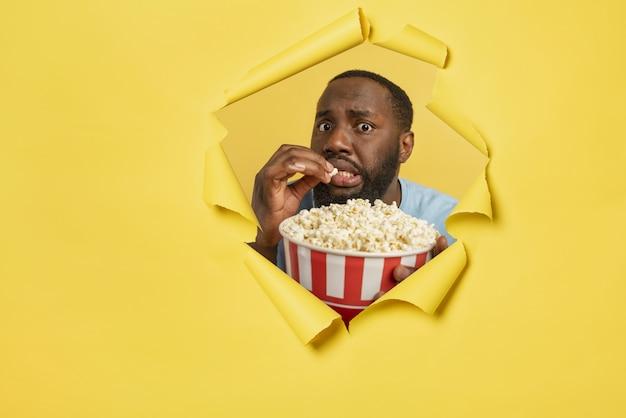 Menino preocupado assiste a um filme de terror atrás de um buraco. conceito de entretenimento e streaming tv