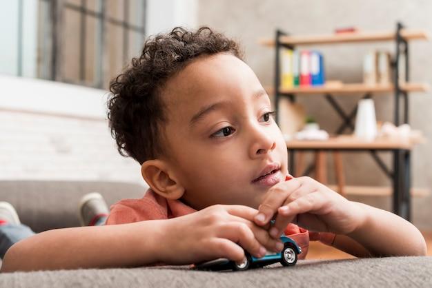 Menino preto pensativo, brincando com o carro de brinquedo