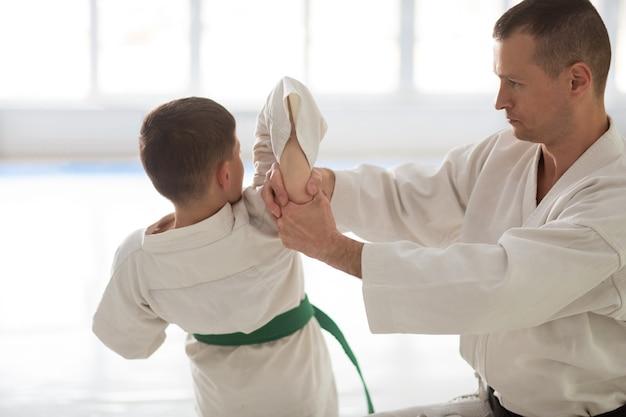 Menino professor. treinador profissional de aikido ensinando menino durante a aula