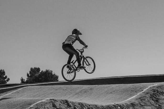 Menino pulando com uma bicicleta bmx em preto e branco em um circuito.