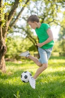Menino pulando com uma bola de futebol na natureza