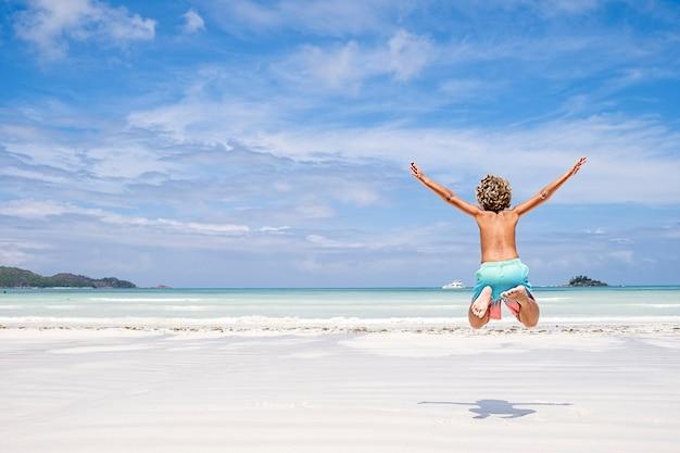 Menino pulando de alegria e diversão em uma praia tropical, conceito de férias de verão