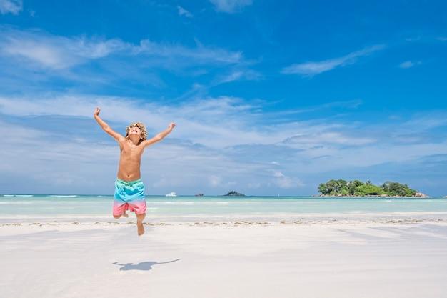 Menino pulando de alegria na praia tropical e no fundo da ilha, conceito de férias de verão