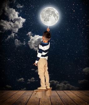 Menino puxando o dedo para a lua