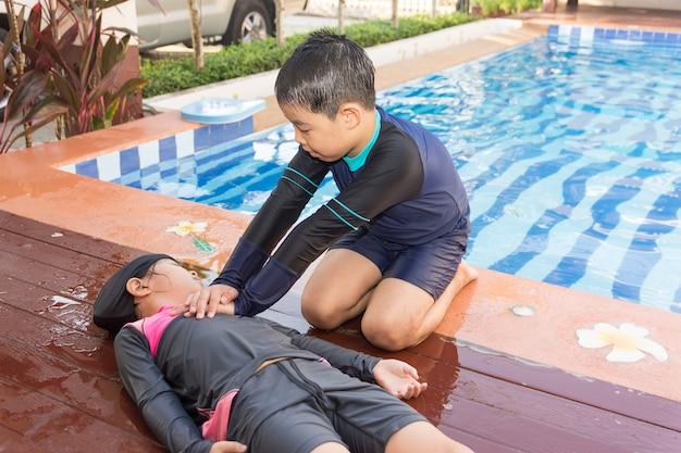 Menino que ajuda afogando a menina da criança na piscina fazendo o cpr.