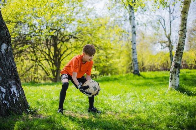 Menino que bloqueia a bola de futebol