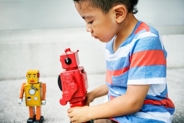 Menino que joga o conceito do divertimento do lazer da apreciação do robô