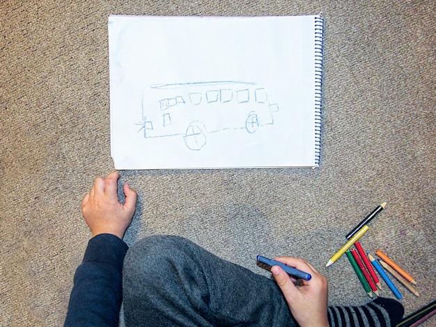 Menino que pinta um ônibus em um papel com lápis de cor