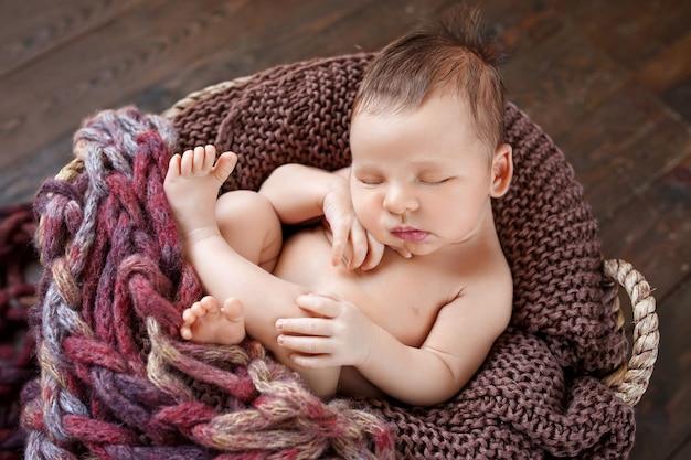 Menino recém-nascido dormindo deitado em uma cesta