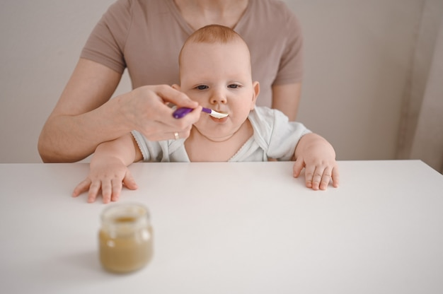 Menino recém-nascido engraçado aprendendo a comer purê de vegetais ou frutas em um frasco de vidro com uma colher