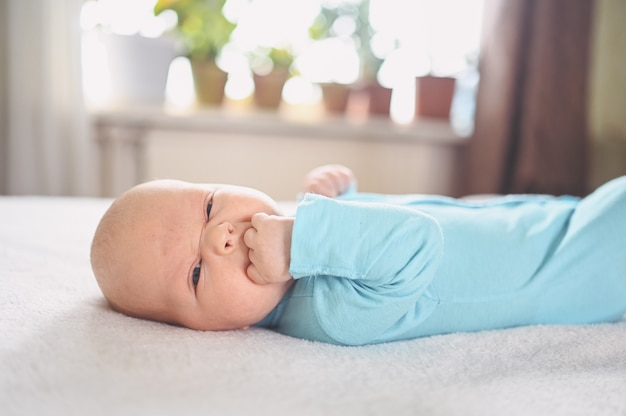 Menino recém-nascido engraçado emocional fofo em macacão azul expressões faciais de bebê infantil berçário