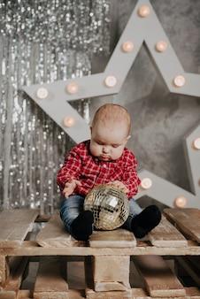Menino recém-nascido feliz sentado no fundo da decoração de natal