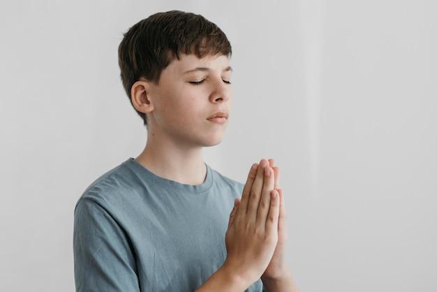 Menino rezando dentro de casa