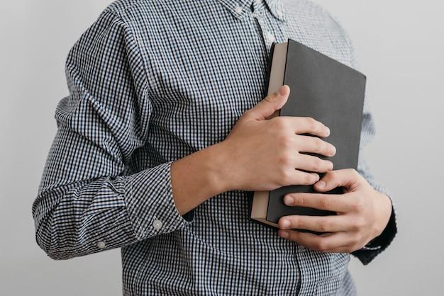 Menino rezando enquanto segura um livro sagrado
