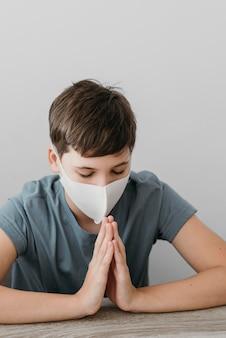 Menino rezando enquanto usa uma máscara médica dentro de casa