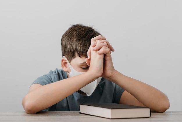 Menino rezando enquanto usa uma máscara médica
