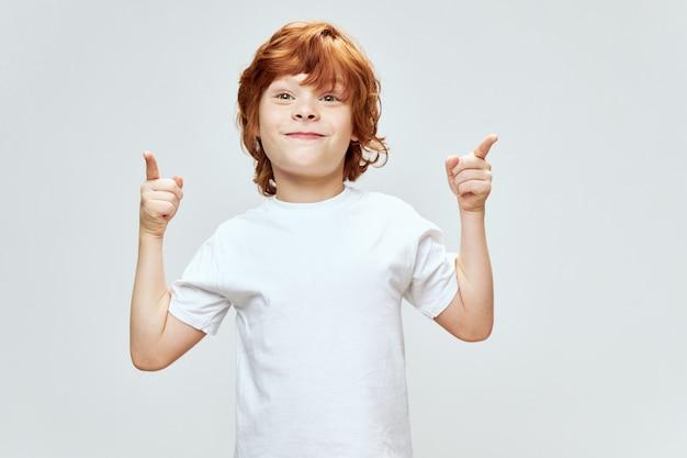 Menino ruivo alegre gesticulando com os dedos indicadores das mãos sorriso t-shirt branca fundo cinza espaço de cópia.