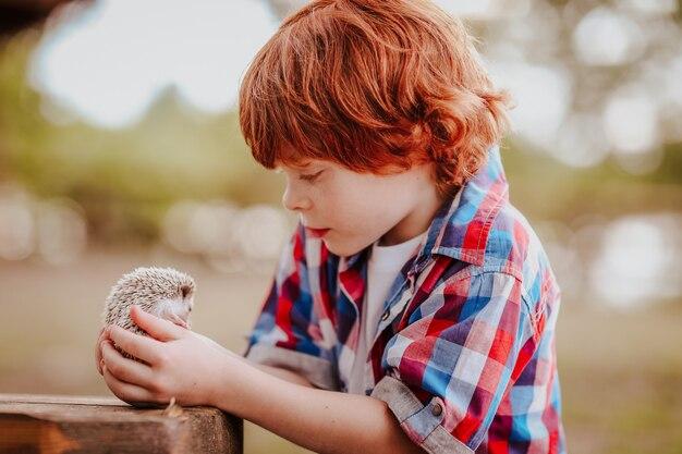 Menino ruivo com ouriço nas mãos