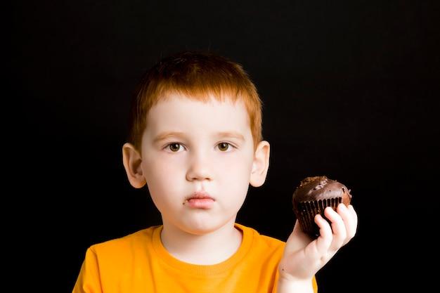 Menino ruivo com um bolinho de chocolate, um menino come um bolinho com prazer, comida doce prejudicial, mas deliciosa em uma criança