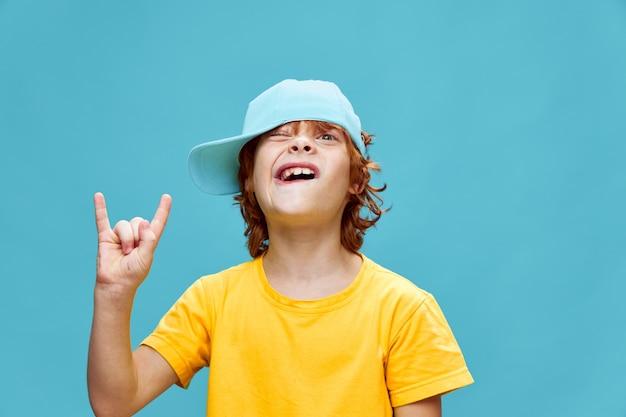 Menino ruivo com um boné na cabeça mostrando um gesto divertido com a mão na moda