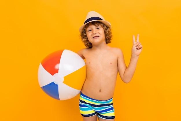 Menino ruivo com um chapéu de verão e um círculo de natação em um fundo amarelo