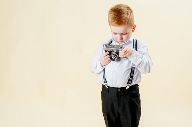Menino ruivo com uma câmera retro nas mãos