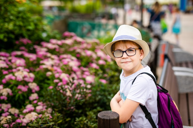 Menino ruivo de chapéu e óculos grandes no parque