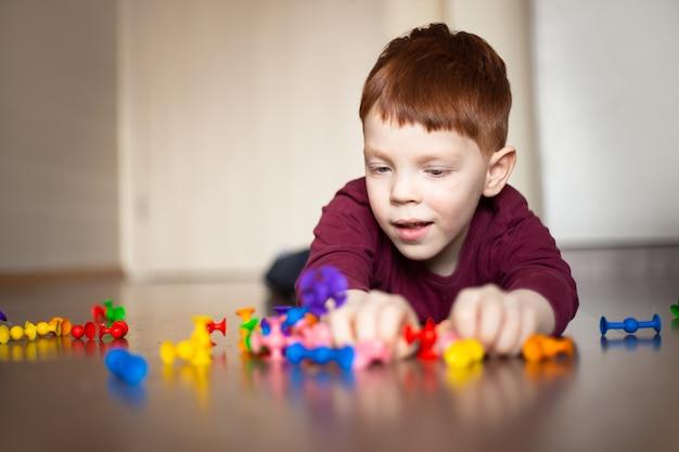 Menino ruivo em uma camisola multicolorida jogando
