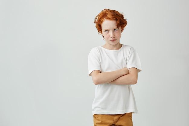 Menino ruivo lindo em t-shirt branca, olhando de lado sendo insatisfeito