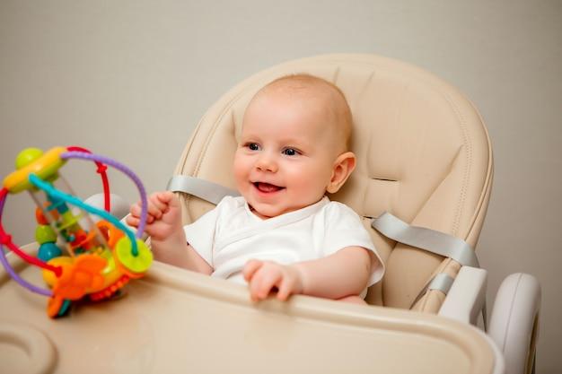 Menino saudável com olhos azuis se senta em uma cadeira alta e brinca com um brinquedo educacional