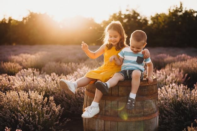 Menino se divertindo com sua irmã mais velha sentado em um barril com um campo de lavanda no fundo