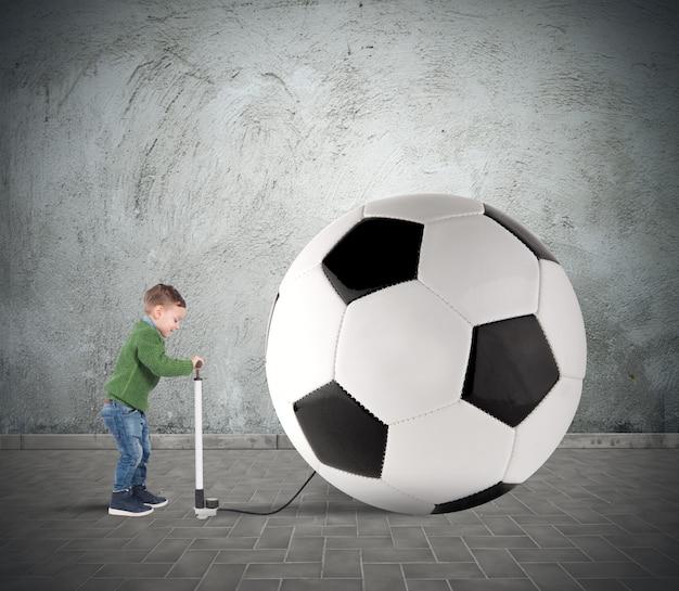 Menino se divertindo com uma grande bola de futebol inchada